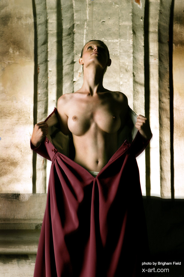busty X-Art model poses topless in cathedral